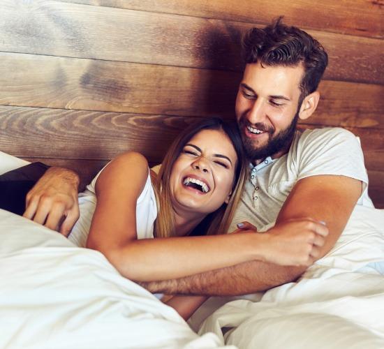 pareja riendo en la cama