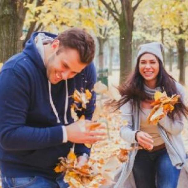 pareja jugando con las hojas que caen durante la temporada de gemelos